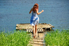 Girl running towards the river. Young white woman running on a wooden bridge towards the river Royalty Free Stock Photos