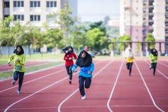Girl running on track Stock Photos