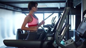 The cute girl is running on a treadmill. The girl is running on the treadmill. At first she holds her hands to the treadmill and then she releases her hands. The stock footage