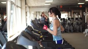 Young sporty girl running on the treadmill at the gym. Girl running on the treadmill in the fitness room. young woman doing aerobic exercises. Exercising in the stock footage