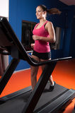 Girl running on treadmill in the gym. Stock Photos