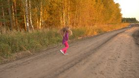 Girl running and twisting on country road autumn evening. Outdoors young girl full length panning. Girl running and twisting on country road autumn evening stock footage
