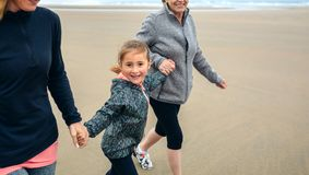 Girl running with two women on the beach. In autumn Stock Photography