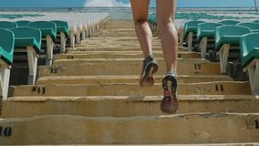 Girl running upstairs at a stadium. Close-up stock footage