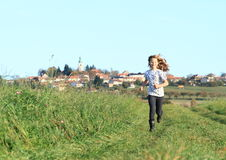 Girl running from village Royalty Free Stock Photography
