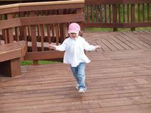 Girl running on walkway Stock Image