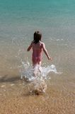 Girl running into the water. Young girl runs into the water with a big splash stock images