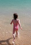 Girl running into the water. Young girl runs into the water with a splash royalty free stock image