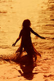 Girl running in the water. Woman running in the water at sunset Royalty Free Stock Image