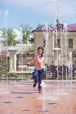 Girl running through the water jets in a fountain. Royalty Free Stock Photo