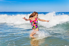 Girl running from the waves Stock Photos