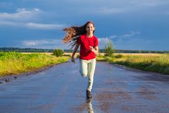 Girl running on wet road. Happy girl running on wet road after rain Royalty Free Stock Images