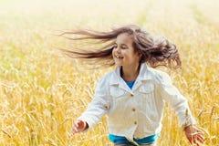 Girl running on the wheat field Stock Photos