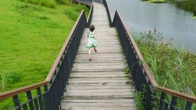 Girl running on the wooden footbridge Stock Photos