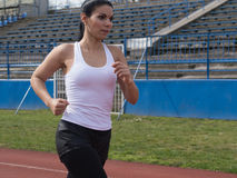 Girl runnning. Shapely sexy black haired woman in white tights running in the sports facility Royalty Free Stock Photo