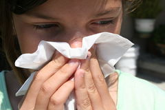 Girl With a Runny Nose. Girl with a cold holding up a tissue to her nose Stock Photography
