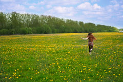 Girl runs. On a glade with flowers Royalty Free Stock Images