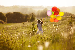 Girl runs across the field with inflatable balls Royalty Free Stock Photo