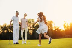 The girl runs across the golf course towards the man and woman who stand in front of her and golf clubs. A girl in a white dress runs along the golf course to royalty free stock photography