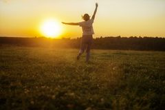 The girl runs against the sunset. In jeans and a white T-shirt. sunset against the background of the forest. summer. heat. happiness. joy. sunset. sunrise Royalty Free Stock Photo