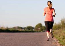 Girl runs along the asphalt road Stock Photography