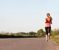 Girl runs along the asphalt road Stock Image