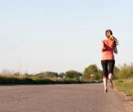 Girl runs along the asphalt road Stock Image