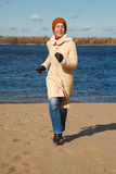 Girl runs along beach autumn day. Stock Images