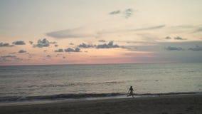 Girl runs along the beach enjoying the sunset stock footage