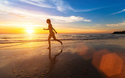 Girl runs along the beach at sunset background. Fitness. Stock Image