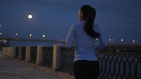 Night jogging. a girl in sports clothes runs along a deserted night embankment in the background of a night city. back