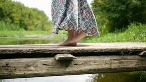 Girl runs along the foot bridge over the river stock footage