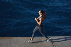 Girl runs along the pier on a warm evening. Full length portrait of beautiful young woman running along the cement pier with amazing big ocean waves on royalty free stock image