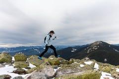 Girl runs along the rocks on the mountain top Stock Photography