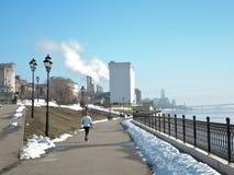 The girl runs along the spring embankment on a spring day royalty free stock photos