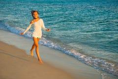 Girl runs along the surf line Stock Photo