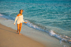 Girl runs along the surf line. Beautiful young girl with long hair walking along the sea. surf line on a beach walk. Young girl on the beach in the sunset Royalty Free Stock Photos