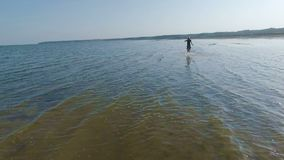 A young and beautiful girl runs barefoot across the surface of the water. Slow-motion shooting by a drone. stock video