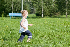 Girl runs around the green grass Stock Image