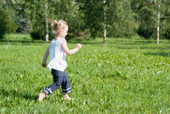 Girl runs around the green grass Stock Images