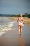 The girl runs away to the beach. Young women are walking in the sand on the beach close to the water Royalty Free Stock Photos