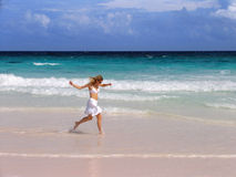 Girl Runs on the Beach. A beautiful blonde woman in a white skirt and bikini runs on the beach as the waves splash at her feet Royalty Free Stock Image