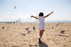 Girl runs on the beach dispersing birds seagulls. And they fly Stock Image