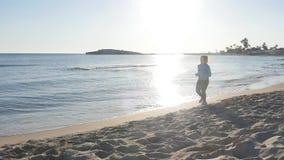 The girl runs on the beach stock footage