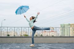 A girl runs behind an umbrella against the backdrop of the city royalty free stock photo