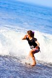 Girl runs from big waves Stock Photos