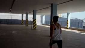 A girl runs in a car park. A girl runs in a car park stock footage