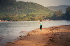 Girl runs from distance on beach at low tide Royalty Free Stock Image