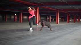 The girl runs with the dog breed Doberman on distillation