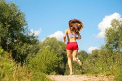 Girl runs in forest from back Royalty Free Stock Image